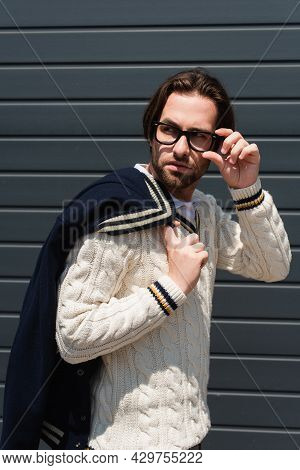 Stylish Man In White Knitted Pullover Adjusting Eyeglasses While Looking Away Outdoors