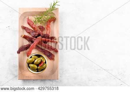 Jerky Meat Strips With Spices And Herbs On Wooden Plate On A Grey Stone Background. Tipical Italian