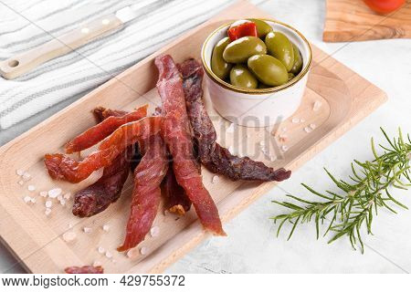 Jerky Meat Strips With Spices, Green Olives, Rosemary On Wooden Plate On A Grey Stone Background. Ti