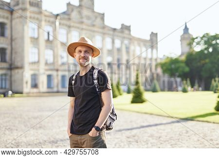Attractive Male Traveler Wearing Backpack And Hat With European City Center Background. Travel, Wand