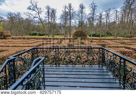 Small Metal Tower In The Middle Of The Maze Formed By Brown Leaf Bushes With Bare Trees In The Backg