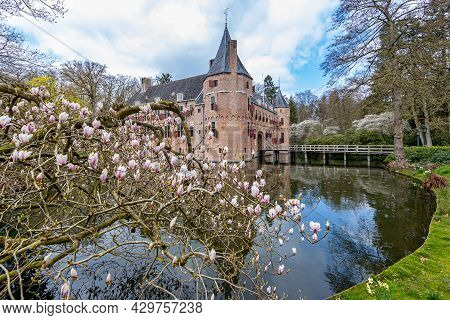 Pink Flowering Plants With The Castle Of Het Oude Loo With Its Moat With Reflection In The Water And