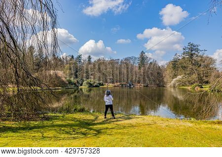 Lake With Reflection In The Water Surrounded By Bare Trees, Mature Woman With Back To Camera Admirin