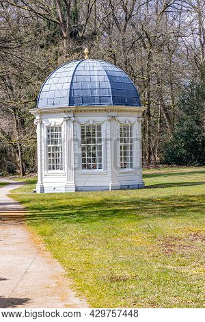 Tea Dome Or Theekoepel Or Gloriette Next A Dirt Trail, Green Grass And Bare Trees In The Background,