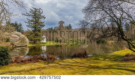 Bare Trees, Pine Trees And Green Vegetation Surrounding A Lake With Reflection In The Water Surface,