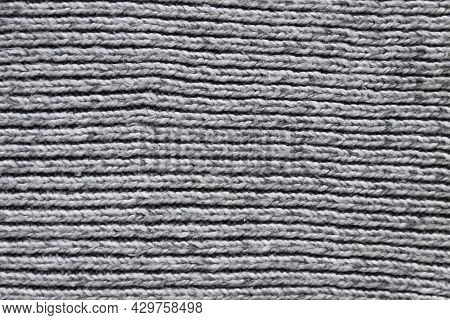 Woolen Knitted Surface Of Grey Textile Close Up. Natural Textile Background. Heavy Knitting Pattern.