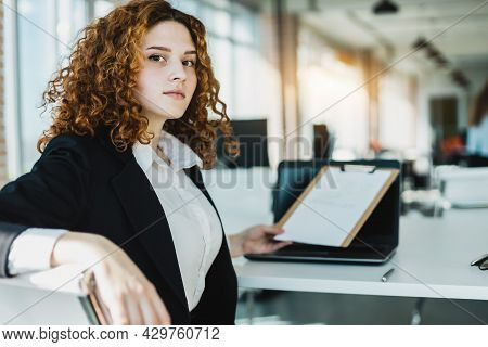 Portrait Of A Beautiful Young Business Woman With Red Curly Hair Working Productively In The Office.