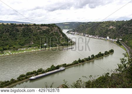 Barge With A Covered Deck Sailing On The River Rhine In Western Germany, Visible Buildings On The Ri