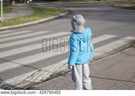Little Boy Is Going To Cross Zebra Crossing. Child Crossing The Road At Pedestrian Crossing In The C