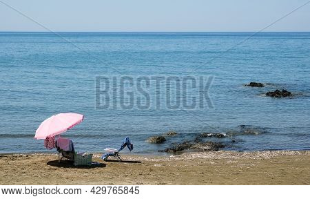 Beach Umbrella And Relaxing Chair On A Sandy Coast In Summer. Summertime Holidays Paphos Cyprus