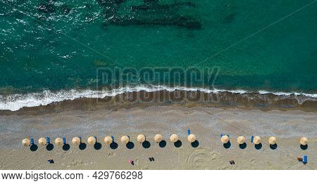 Aerial View From A Flying Drone Of Beach Umbrellas In A Row On An Empty Beach With Braking Waves. Pa