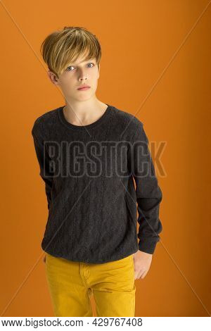 Stylish Blond Handsome Teenage Boy. Attractive Boy Wearing Gray Pullover And Pants Posing Against Oc