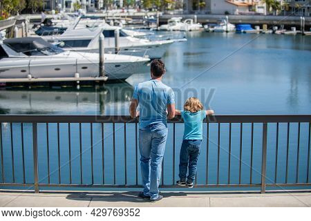 Parenting And Fatherhood. Fathers Day. Father And Son Looking At Yachts In Harbor.