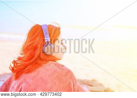Pretty Woman Listening To Music On The Beach. Redhead Girl Listening To Melody With Listening Device