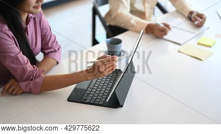Two Business Partners Are Discussing Financial Report With Computer Tablet In Meeting Room.