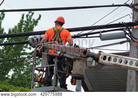 Lineman Who Repairs Power Electric Cables In Articulated Boom Lift