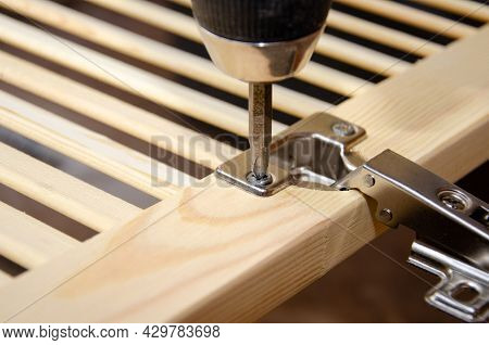 Twisting The Self-tapping Screw Into The Door Hinge With A Screwdriver. Door Hinge Installation.