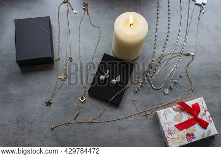 Modern Golden Accessories, Vintage Candles And Boho Mirror On White Table. Stylish Gold Ring, Chain