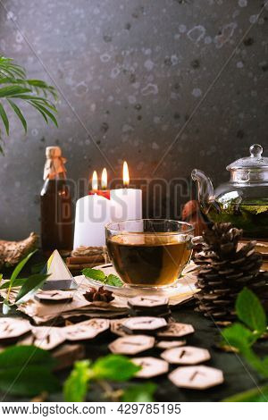 Wooden Runes Are Lying On The Table Among The Papers With Notes. There Is A Mug Of Tea Next To It. A