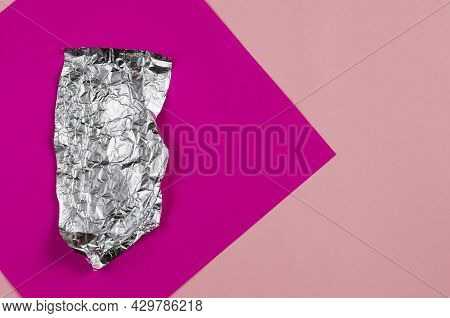 Geometric Composition With Crumpled Foil Against A Purple And Pink Background. A Piece Of Aluminum F