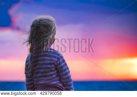 Back View Of Unrecognizable Blonde Child Girl Stands And Looks At Setting Sun Against Bright Sunset