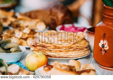 Dishes Of The Traditional Belarusian Cuisine - Pancakes And Pickled Cucumbers. Attribute Of Traditio
