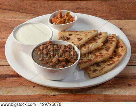 Aloo Paratha Or Indian Potato Stuffed Flatbread And Channa Masala Served With Fresh Curd And Pickle.