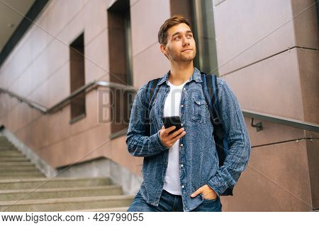 Low-angle View Of Portrait Of Handsome Delivery Man With Thermo Backpack Holding Using Mobile Phone