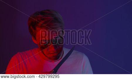 Angry Man, Maniac Or Crazy, Licks A Knife Standing In A Dark Room. Portrait Man With A Knife. Concep