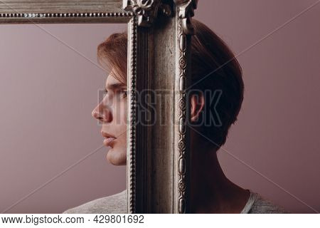 Millenial Young Man Close Face With Gilded Picture Frame Portrait.