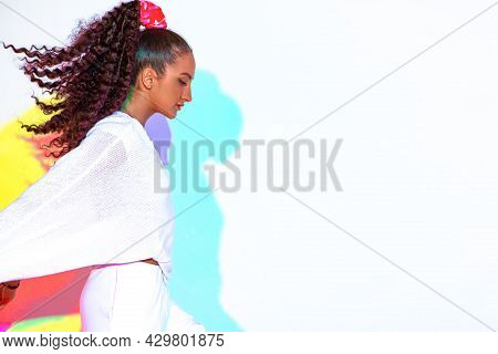 Stylish Mixed Race Young Girl In Colourful Rainbow Studio Light On White Background. Modern Female W
