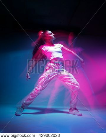 Dancing Mixed Race Young Girl In Colourful Neon Studio Light. Female Dancer In White Stylish Sportsw
