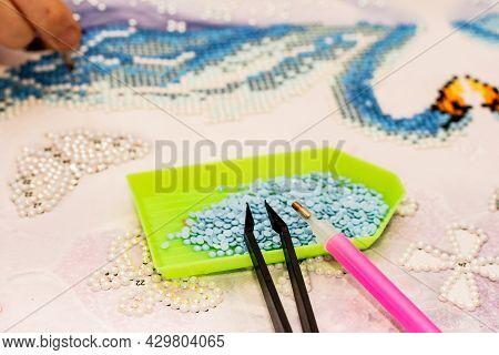 Diamond Painting Embroidery Craft. Acrylic Rhinestones, Pen And Tweezers. Closeup, Selective Focus.