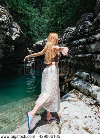A Longhaired Girl Stands In A Swallow Pose Near A Turquoise River In A Rocky Environment On A Sunny