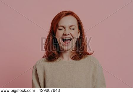 Overjoyed Red Haired Caucasian Woman Laughing Positively, With Closed Eyes, Expressing Positive Emot