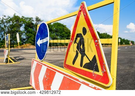 Road Works Sign On The Road. Repair Work Of Road Signs And A Bypass Arrow On A Background Of Blue Sk