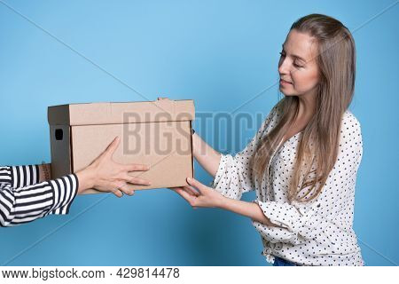 You Send, Transfer And Accept A Box With A Parcel From Hand To Hand, A Young Woman Receives A Gift O