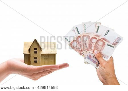 Closeup Hand A Man And A Woman Holding A Money Bank And A Model Home On Blurry Background. Home Loan