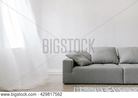 Sofa In Living Room Interior, Home Design. Modern Apartment With Grey Couch Stand Near Window. Comfo