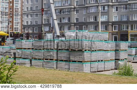 There Are Many New Gray Paving Slabs On Plastic-covered Pallets On The Construction Site. Paving Of