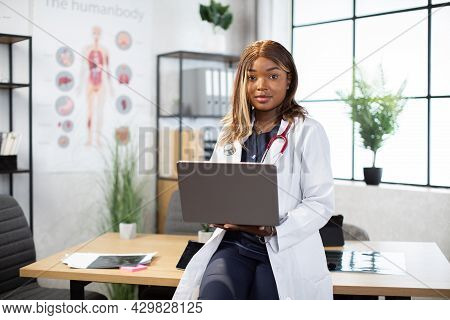 Black Female Doctor Wearing White Coat And Scrubs At Work In Modern Medical Office, Leaning At The T