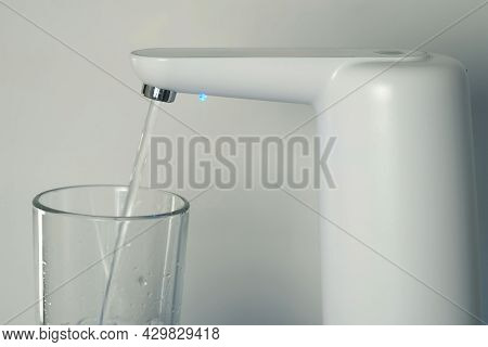 Clear Water Is Pouring Into Glass From An Automatic Water Cooler, Closeup View. Pouring Fresh Clear