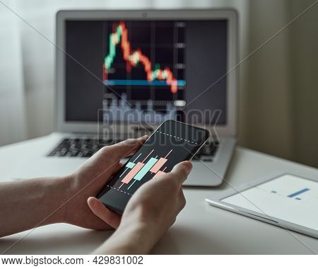 Millennial Unknown Male Analysing Graphs And Data On Laptop And Smartphone At Office. Online Trader