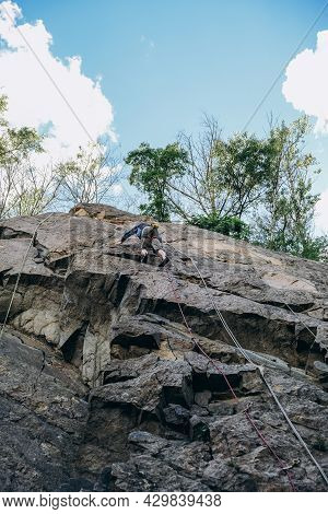 A Little Boy Is Engaged In Mountaineering. The Boy Climbs The Rock On A Rope. Climbing Training. Chi