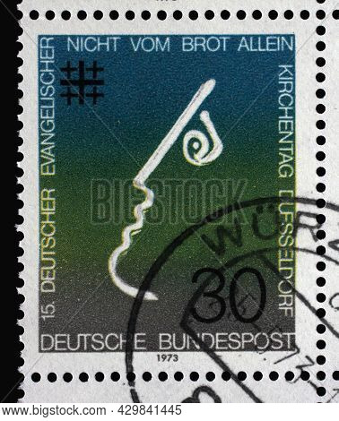 ZAGREB, CROATIA - SEPTEMBER 11, 2014: Stamp printed in Germany showing a stylized face and a cross, Not by Bread alone, 15th meeting of German Protestants (Evangelical Synod) in Dusseldorf, circa 1973