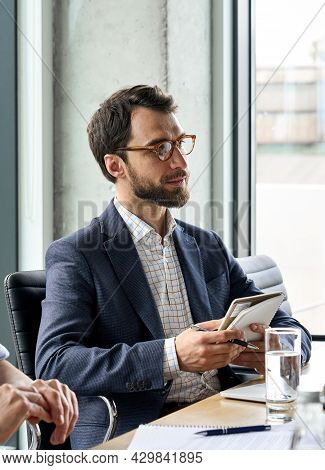 Serious Caucasian Bearded Male Ceo Wearing Suit Looking At Colleague Discussing Corporation Strategy