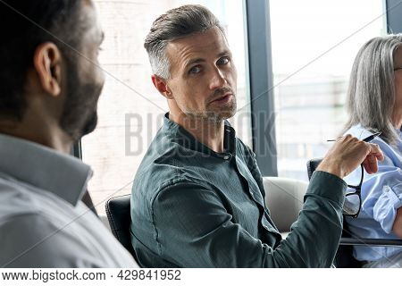 Mature Male Ceo Talking Looking At African American Manager Sitting At Table In Boardroom. Multiraci