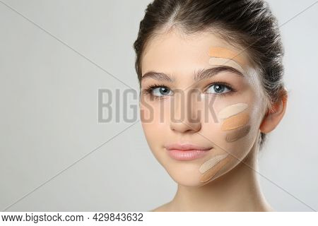 Beautiful Girl On Light Grey Background. Using Concealer And Foundation For Face Contouring