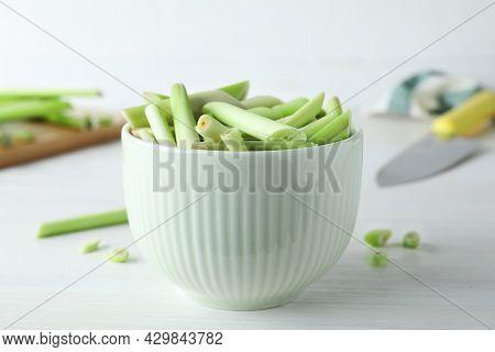 Bowl With Fresh Lemongrass Stalks On White Table, Closeup