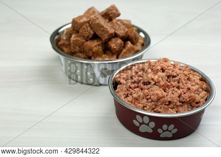 Different Pet Food In Feeding Bowls On White Wooden Background